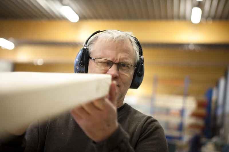 Man med hörselkåpor granskar en träplanka inför hustillverkning.