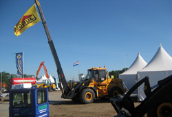 Hjullastare med kran som hissat Ljungby maskins flagga.
