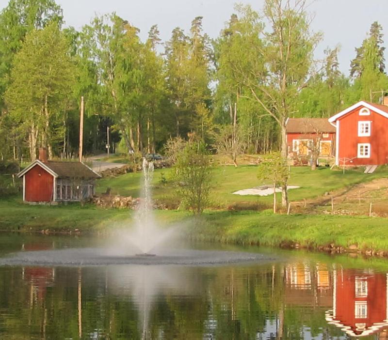 Kasco flytande fontän i damm framför rött hus med vita knutar på landet.